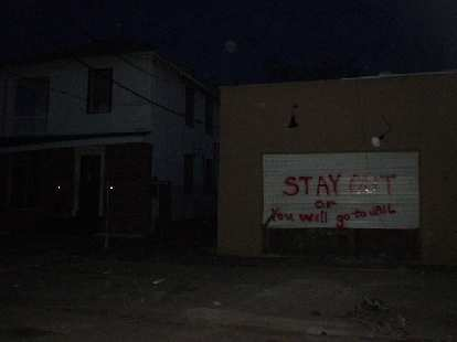 """Along the same street as the hostel were homes boarded up declaring various things such as """"Stay out or you will go to jail""""."""