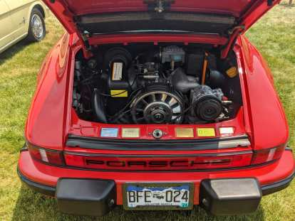 The engine bay of a red air-cooled Porsche 911.
