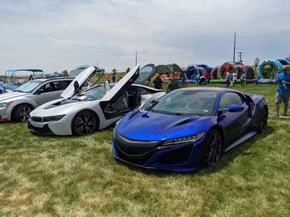 A blue Acura NSX (circa 2020) with a white BMW i8 and a silver Dodge Caliber.
