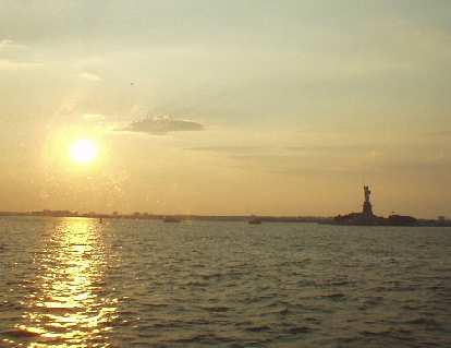 The view of the Statue of Liberty from the ferry, as lit by a dawning sun.
