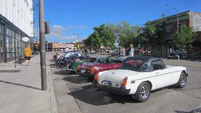 white rubber-bumpered MGB roadster with top up, British sports cars, downtown Fort Collins