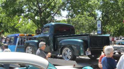green vintage Ford pickup truck on tow truck bed
