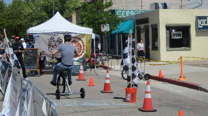 man riding tricycle on coned course at Fort Collins Old Town Car Show