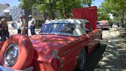 salmon-colored 1950s Ford Thunderbird convertible with white top