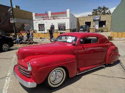 A red 1947 Ford coupe hot rod.