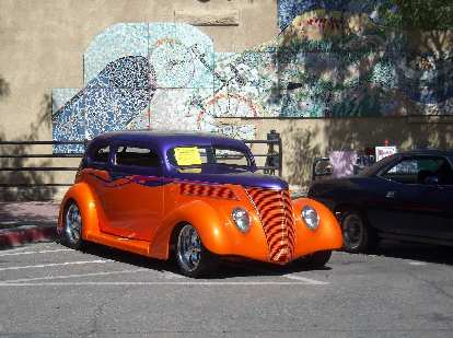 An orange and purple hot rod based off a Ford Sedan of the 1930s, with a nice tile mural behind.