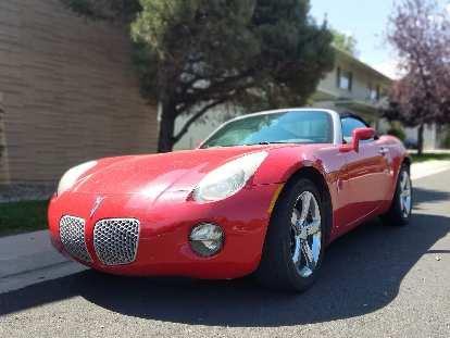 A nice red Pontiac Solstice roadster.