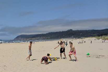Some guys playing Spikeball (roundnet) on Cannon Beach, Oregon.