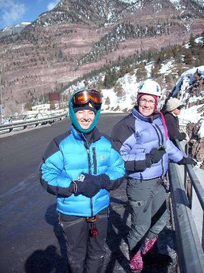 Tori and Michele taking photos of climbers in the Uncompahgre Gorge on a bridge.