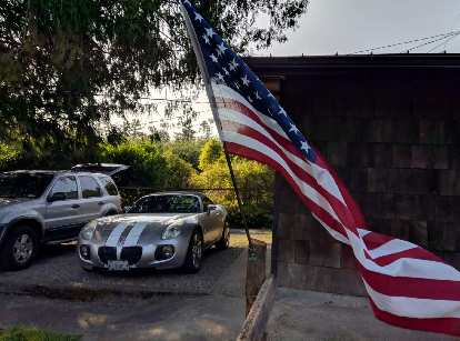 An American flag flying outside the house Erin and Russ are renting, with their silver Mercury Mariner and my silver Pontiac Solstice GXP rental car.
