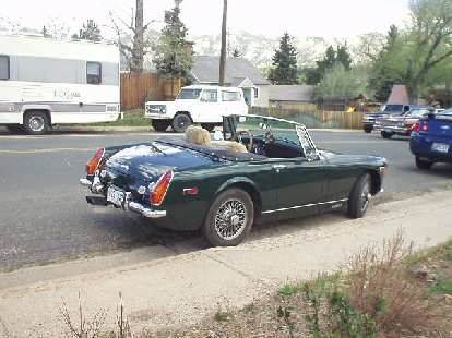 A diminutive MG Midget, probably a '71 (note the round rear fenders).