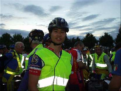 [>1 hour before the race, 8:50 p.m.] Here I am, with mandatory reflective vest, in a huge horde of riders who are also all set to go.