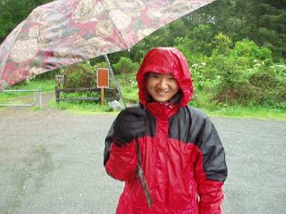 At the Sky Trailhead parking lot, here's Merry with here colorful umbrella and all set for a hike in the rain.