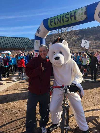 The polar bear mascot in position to pace the lead runners of the 2019 Polar Bear 5k Run on a bicycle.