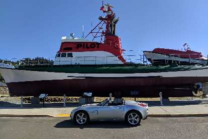Silver Pontiac Solstice GXP in front of a Pilot ship in Astoria, Oregon.