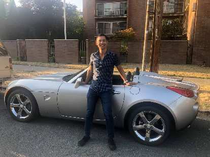Felix Wong with the silver Pontiac Solstice GXP he rented in the Pacific Northwest.