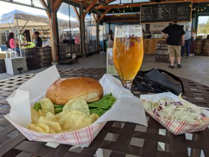 burger, chips, coleslaw, and beer at Allagash Brewing Company