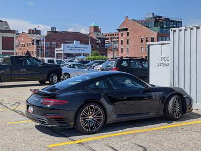 """A black 911 Turbo (991 Series) parked in downtown Portland, Maine with a sign reading """"May you have fair winds and following seas."""""""