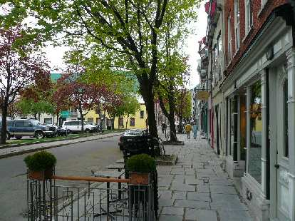 Sidewalk paved with rectangular pavers along storefronts in Quebec City.