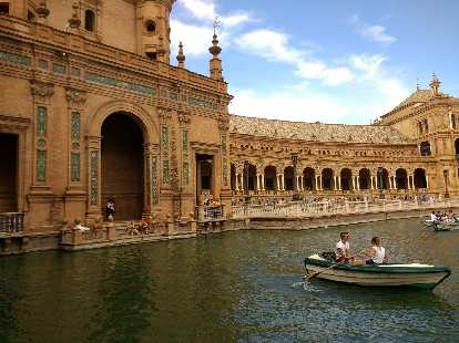A woman rowing a canoe in the canal at the Plaza de España in Seville, Spain.