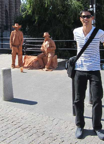 Felix Wong in front of some orange men near the Swedish Parliament.