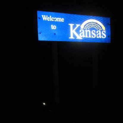 blue Welcome to Kansas sign, night