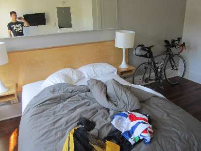 Cycling clothes on bed and black Litespeed Archon C2 in cabin room of Norblad Hotel in Astoria, Orego.