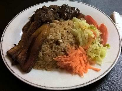 An entrée of oxtail, brown rice, carrots and cabbage at Nicolette's Caribbean Café in Tampa, Florida.