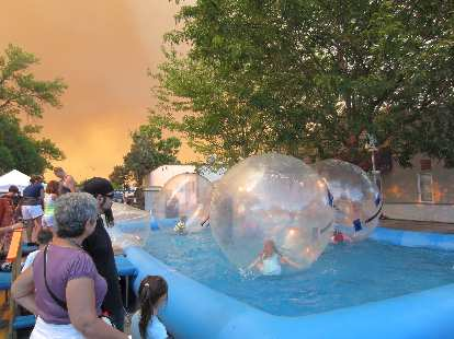 Kids in air bubbles in a giant pool.  Note the orange sky due to smoke from the High Park Fire.
