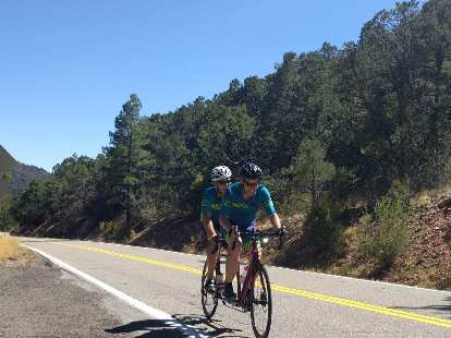 Chris Scott and Dan Berlin cruising on a pine tree-lined road in southern Colorado.