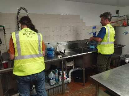 Matt Hannifin and Nate Faudel (both RV drivers for Team Sea to See) helping wash dishes inside the kitchen of a random restaurant in Pagosa Springs.