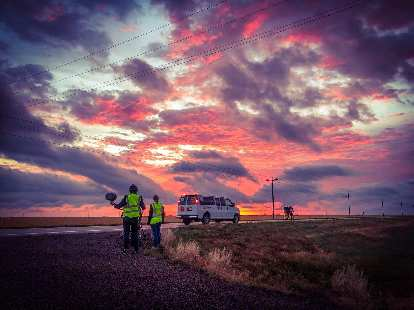 A nice sunrise in Kansas while a person from Team Sea to See's media crew and Sheila Stevens (navigator) look on.