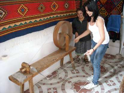 Ojudju trying to spin yarn on a spinning wheel.  It was harder than it looks.