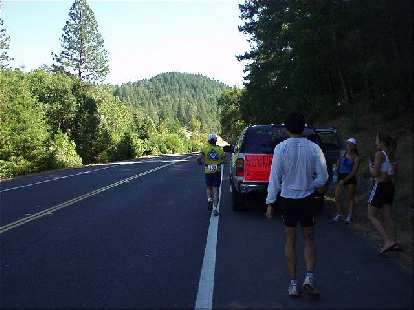 [Mile 6, 1:06 elapsed, 1:36 p.m.] As we would do for almost every leg, we stopped off midway to offer water and support.  That's Phil running with Everitt, Lisa, and Heidi cheering on.  You can see the gas-guzzling Chevy Tahoe with non-folding middle seat in this picture too.