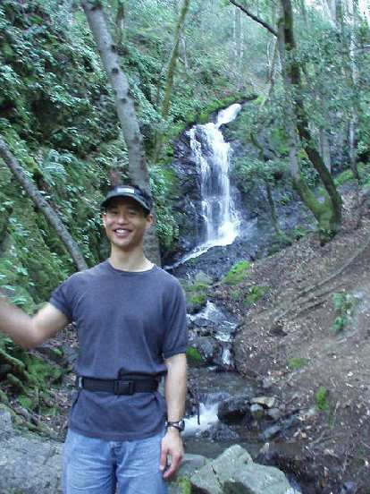 Felix Wong gives a wave in front of the same waterfall.