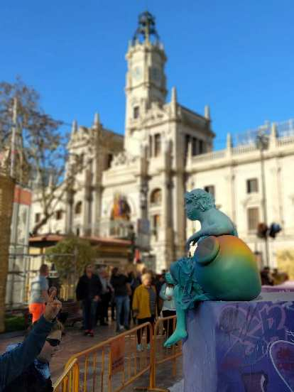 A smaller green ninot (a caricature of something usually made of paper and wax) with Valencia's City Hall in the background.