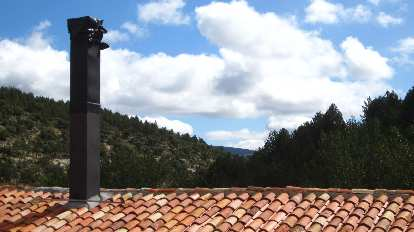 Clouds, mountains and tile roof at Valdelavilla.