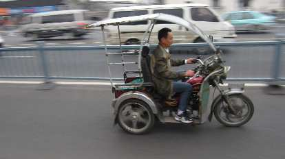 Three-wheeled motorized vehicle with roof in Suzhou.