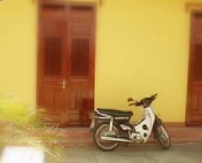A white/black Honda Super Cub motorbike in front of a yellow home in Vietnam.