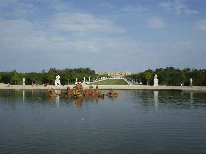 Small man-made lake (pond) with bronze, Apollo-like horse and chariot statues in the middle.