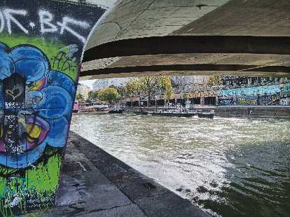 Colorful graffiti on a bridge support by the Wien River