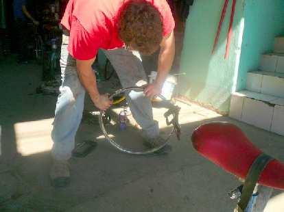 "Patrick bending rebar around a 24"" wheel to make a cage for a new bicimacadamia machine."