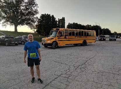 Manuel with one of the yellow school buses that took runners to the start of the 2019 Wabash Trace Trail Marathon.
