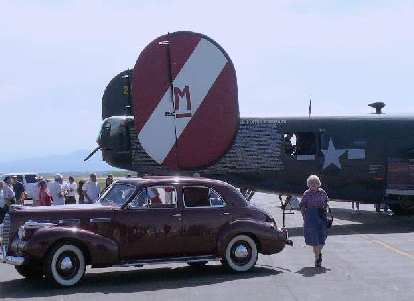 A LaSalle sedan in front of a B-24.