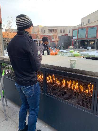 Felix warming up by the fire at the Exchange in Old Town Fort Collins during Winter Bike to Work Day.
