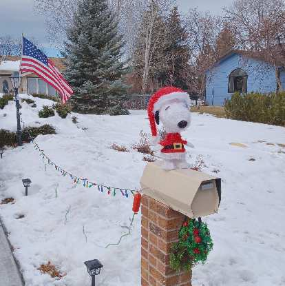 Snoopy dressed up in a Christmas costume on top of a mailbox, as seen while biking back home on Winter Bike to Work Day.