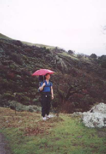 [Ohlone Wilderness Trail, Jan 2002] Felix Wong experimenting with using an umbrella during the 15-mile rain hike into camp.  It worked well!