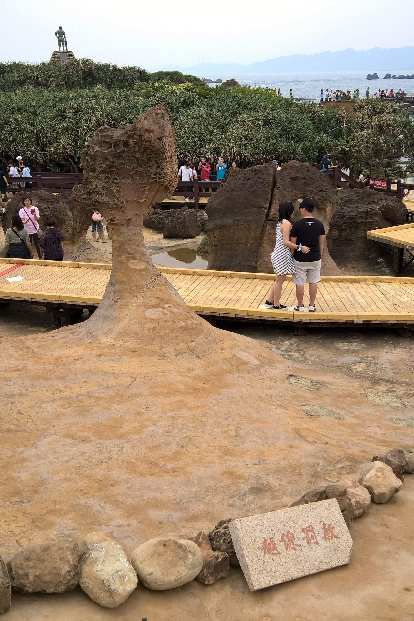 A couple posing by the Queen's Head in Yehliu Geopark in New Taipei, Taiwan.