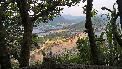 The view of buildings on the Yehliu Peninsula through trees at Yehliu Geopark.