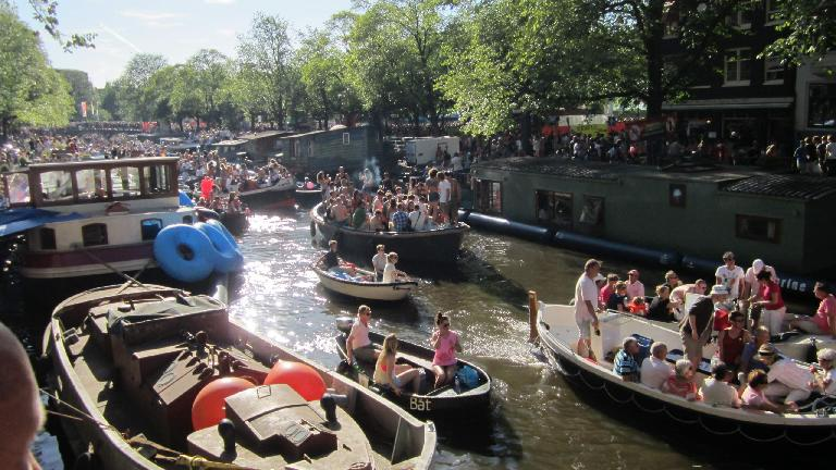 People celebrating on boats on Canal Prinsengracht.